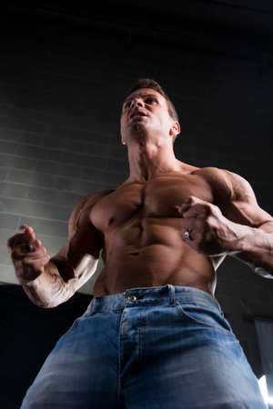 outrage: Low angle close up view of a strong young man with a muscular physique standing clenching his fists to emphasize his arm and shoulders muscles
