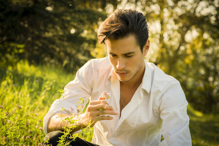 wistful: Nostalgic young man dreaming or reminiscing in the park as he kneels in green grass touching a flower with a look of wistful loneliness Stock Photo