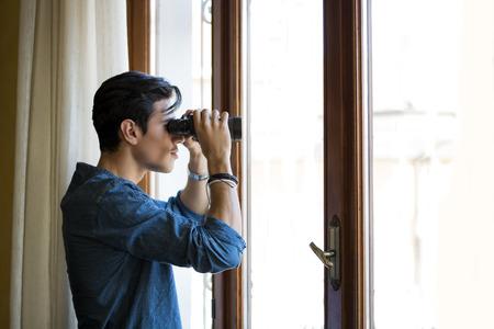 investigación: Hombre joven de pie mirando a través de una puerta de cristal con los prismáticos mientras mira algo en la distancia