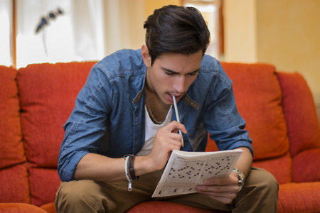 Young man sitting doing a crossword puzzle looking thoughtfully at a magazine with his pencil to his mouth as he tries to think of the answer to the clue