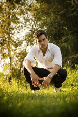 suave: Handsome man outdoors in the garden crouching down on fresh green grass amongst trees looking seductively at the camera