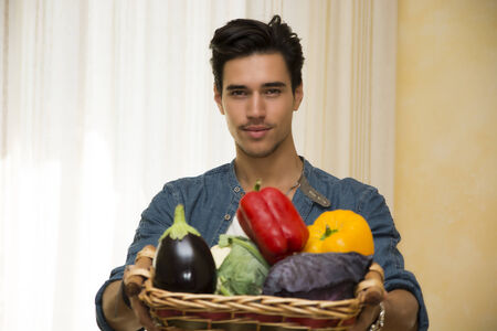 Young man holding a basket of fresh vegetables containing an aubergine, sweet bell peppers and cabbage photo