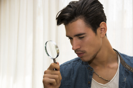 distrustful: Young man looking through a magnifying glass in a conceptual image of a detective searching for clues, inspection, examination or analysis Stock Photo