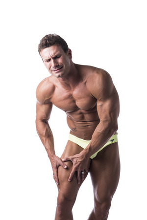 Muscular handsome mature man in underwear holding his leg with both hands and grimacing in pain, isolated on white