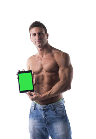 muscular shirtless young man holding a blank tablet PC while looking at camera, portrait on white photo