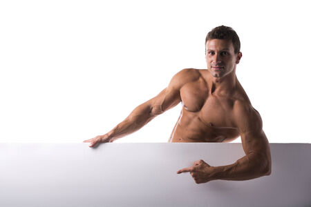 Shirtless muscular young man standing holding a blank horizontal white banner pointing finger at the copyspace photo