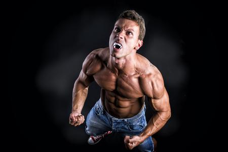 Nackter Oberkörper-Muskel-Mann mit spitzen Zähnen Transforming in Werewolf in Studio mit schwarzem Hintergrund