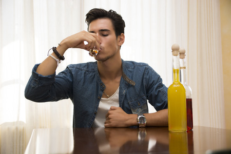 morose: Young man sitting drinking alone at a table with two bottles of liquor alongside him sipping from shot glass to drown his sorrows