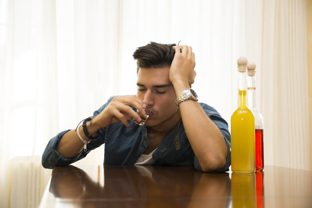jilted: Sleepy, drunk young man sitting drinking alone at a table with two bottles of liquor alongside him sipping from shot glass to drown his sorrows Stock Photo