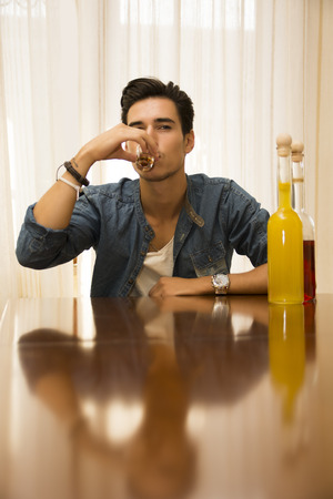 jilted: Young man sitting drinking alone at a table with two bottles of liquor alongside him sipping from shot glass to drown his sorrows
