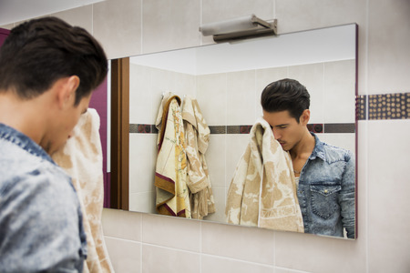 Reflection of Young Man Drying Face with Towel in Mirror as Part of Daily Hygiene Routine photo