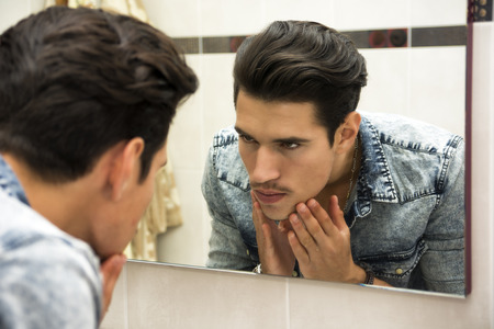 Close Up of Young Man Examining Face in Reflection of Mirror and Glaring at Self