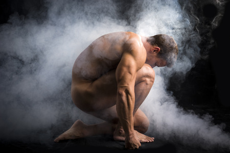 Nude Profile of Young Muscle Man Crouching in Fog in Studio with Black Background Stock Photo
