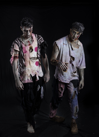 zombies: Two male zombies standing on black background walking towards camera Stock Photo