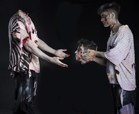Two male zombies, one giving the head to the decapitated ones body, standing on black background