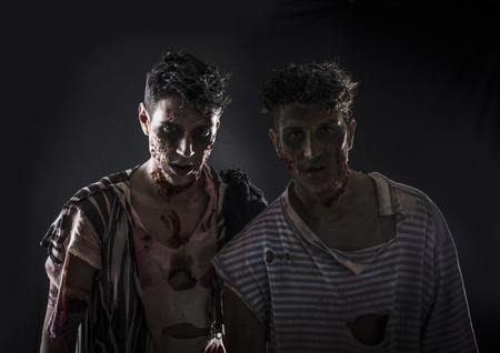 smoky black: Two male zombies standing on black smoky background, head and shoulder shot. Halloween theme Stock Photo