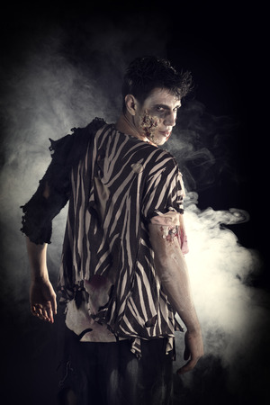 Male zombie standing on black background, turning around looking at camera. Halloween theme Stock Photo