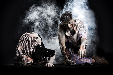 Two male zombies crawling on their knees, on black smoky background, looking at camera. Halloween theme photo