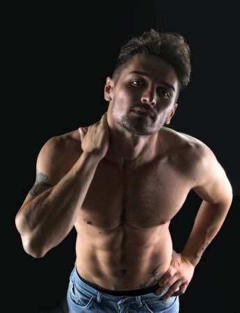 Handsome shirtless muscular man shot from above, isolated on black background, looking up at camera photo