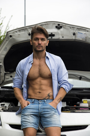 shirt unbuttoned: Macho uomo bello con la camicia sbottonata per mostrare il suo corpo muscoloso appoggiato con noncuranza contro la griglia della sua auto con il cofano aperto Archivio Fotografico