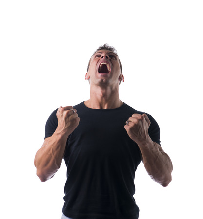 Young Angry Muscled Man, Shouting with Closed Fists, in Plain Black Shirt, Isolated on White