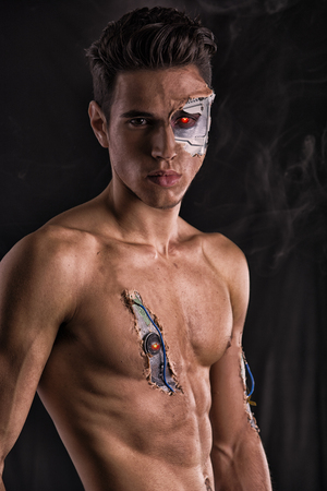 Close up Attractive Bare Muscled Man with Robotic Skin Art Looking at the Camera on Black Background. photo