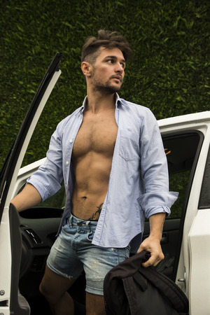 Gorgeous Young Man in Beach Attire Getting Out his Car, Showing Body Abs. Looking to His Left. photo