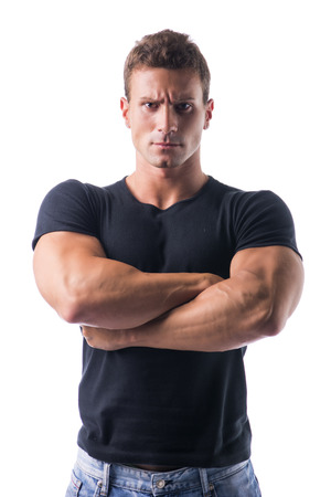unyielding: Confident Young Muscled Man in Black Shirt Crossing Arms in Front of the Camera with Serious Face. Isolated on White . Stock Photo