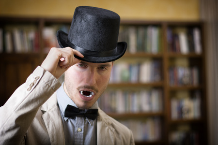 Close up Young Handsome White Vampire with Black Top Hat Inside the Mini Library photo
