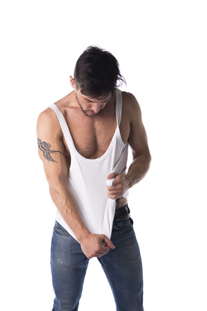 tanktop: Young athletic man pulling down tanktop on ripped muscular torso, isolated on white Stock Photo