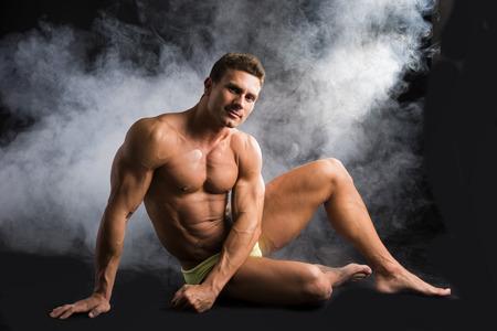 hombre fuerte: Hombre musculoso sin camisa atractiva que se sienta en el suelo en traje de baño en el fondo oscuro