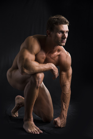 nude man: Totally Nude Young Muscle Man Crouching on one Knee in Studio with Black Background