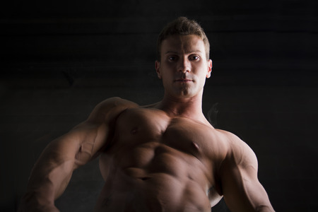 pecs: Handsome shirtless bodybuilder shot from below. Close-up of ripped sexy abs and pecs Stock Photo