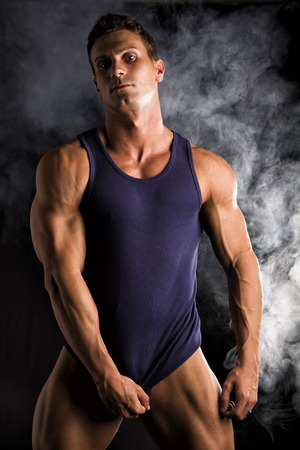 male model torso: Young athletic man pulling down tanktop on ripped muscular torso, on dark smoky background
