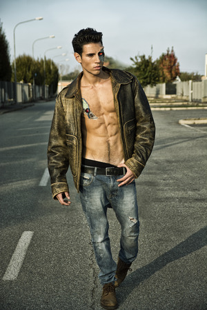 Young Handsome Robotic Man Wearing Leather Jacket Walking in the Street Showing Sexy Body Abs While Looking away Stock Photo
