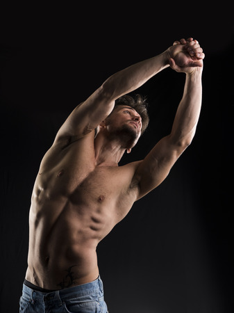 Handsome muscular shirtless young man stretching and looking up to a side, isolated on black photo