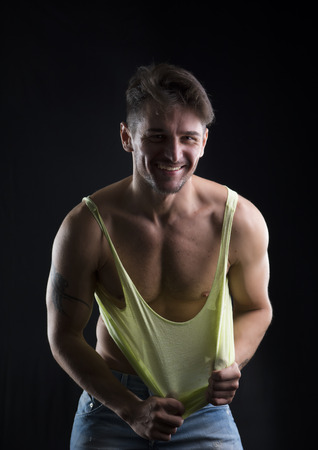 tanktop: Young athletic man pulling down tanktop on ripped muscular torso, smiling isolated on white Stock Photo