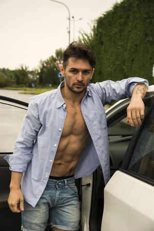 Gorgeous Young Man with Shirt Open on Naked Muscular Torso Getting Out his Car, Showing Sexy Body Abs. Looking at Camera photo