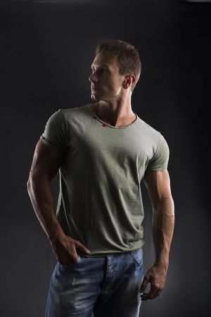 Handsome muscular fit young man on dark background looking to a side photo
