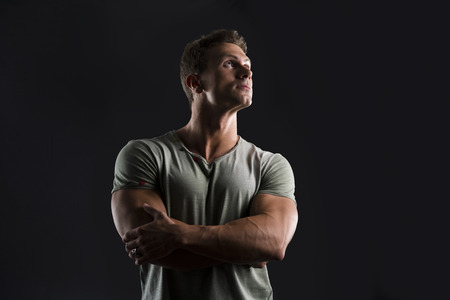 Handsome muscular fit young man on dark background looking up, arms crossed on his chest photo