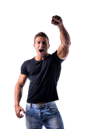 Successful sexy young man with fist raised in the air, looking at camera happy and joyful, isolated on white photo