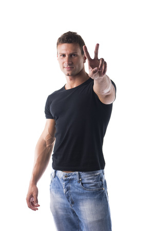 Successful sexy young man doing Victory sign with fingers, looking at camera, isolated on white photo