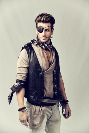 pirata: Hombre apuesto joven en traje de pirata de moda en el fondo gris. Capturado en Studio. Foto de archivo