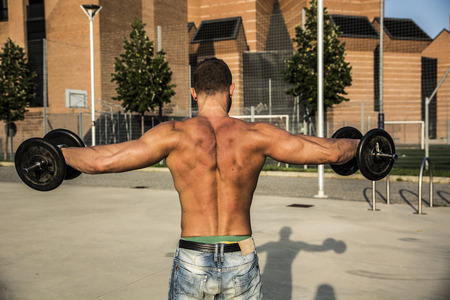 Shirtless Muscular Man Seen from the Back Lifting Weights Outdoor. Showing Healthy Body