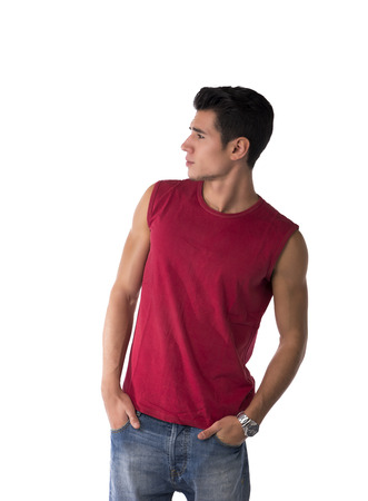 Attractive young man in red sleeveless shirt and jeans, looking to a side at blank space next to him, isolated on white photo