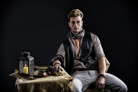 looking up: Good Looking Young Man in Pirate Fashion Outfit Sitting next to Table with Candle Lamp, Compass, Gold