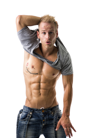 Good Looking Young Gym Fit Man Showing His Sexy Six Pack Abs While Looking at the Camera. Isolated on White Background. photo