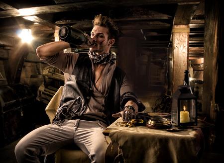 Knappe Rugged Man Pirate drinken van fles in Ship Quarters Stockfoto