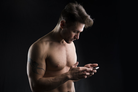 shirtless man: Handsome shirtless muscular young man using cell phone on dark background