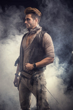 rugged: Good Looking Young Man in Pirate Fashion Outfit on Gray Smoke Background. Captured in Studio. Stock Photo